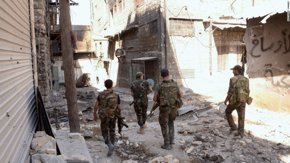 Syrian troops walk down a street Tuesday, September 25, in Aleppo following fighting between government forces and rebels.