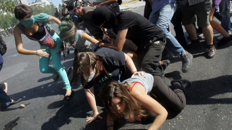 Protesters fall down in the street during clashes on Wednesday.