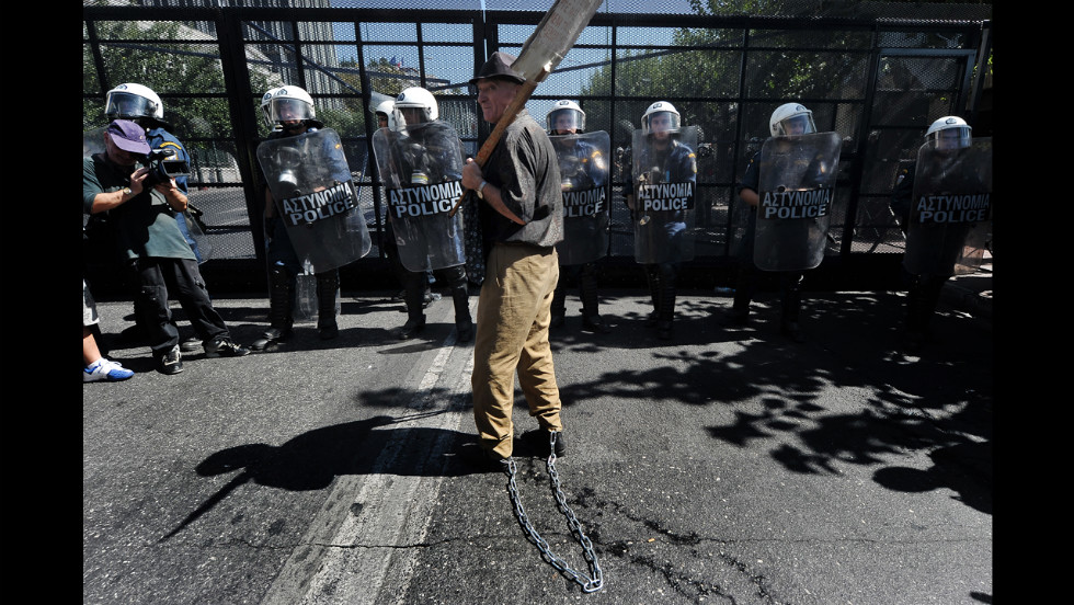 An elderly man with his legs chained stands in front of riot police protecting the Greek parliament Wednesday.