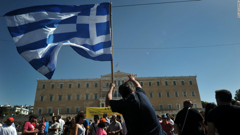 "A protester holding a Greek flag gestures toward parliament in Athens on Wednesday, September 26. Greek trade unions called a 24-hour general strike to oppose new austerity measures. Police said some protesters threw Molotov cocktails in Syntagma Square, opposite the  parliament building. Police responded with tear gas. <a href=""http://www.cnn.com/2012/09/26/europe/gallery/spain-protest/index.html"">See anti-austerity protests in Spain</a>."