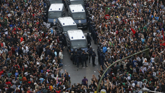 Protesters surround police vans near the Spanish Parliament in Madrid on Tuesday, September 25. Spain