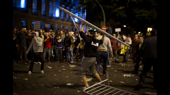 A demonstrator throws a fence toward riot police. Some protesters threw bottles and rocks at officers, who fought back, a state-run broadcaster reported.