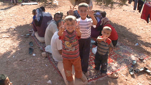Syrian refugees wait with sick children
