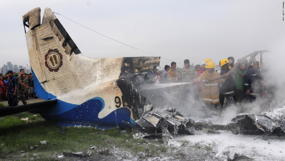Nepalese firefighters and volunteers help put out flames from the wreckage of a crashed Sita Air plane outside Kathmandu, Nepal, on Friday, September 28. The Dornier-built aircraft went down minutes after takeoff from Kathmandu's international airport, reports said. All 19 aboard the plane died, Nepalese authorities said.