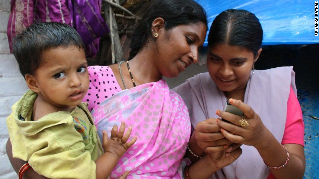 Two women in India using a mobile-based reminder system for vaccinations. b9e136681