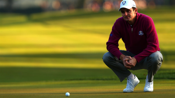 Golfer Justin Rose of Europe lines up a putt on the first green.