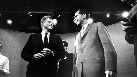 John F. Kennedy and Richard Nixon exchange smiles beneath glaring lights before their first TV debate in 1960.