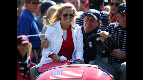 Phil Mickelson of the United States drives with his wife Amy Mickelson on the 16th green.