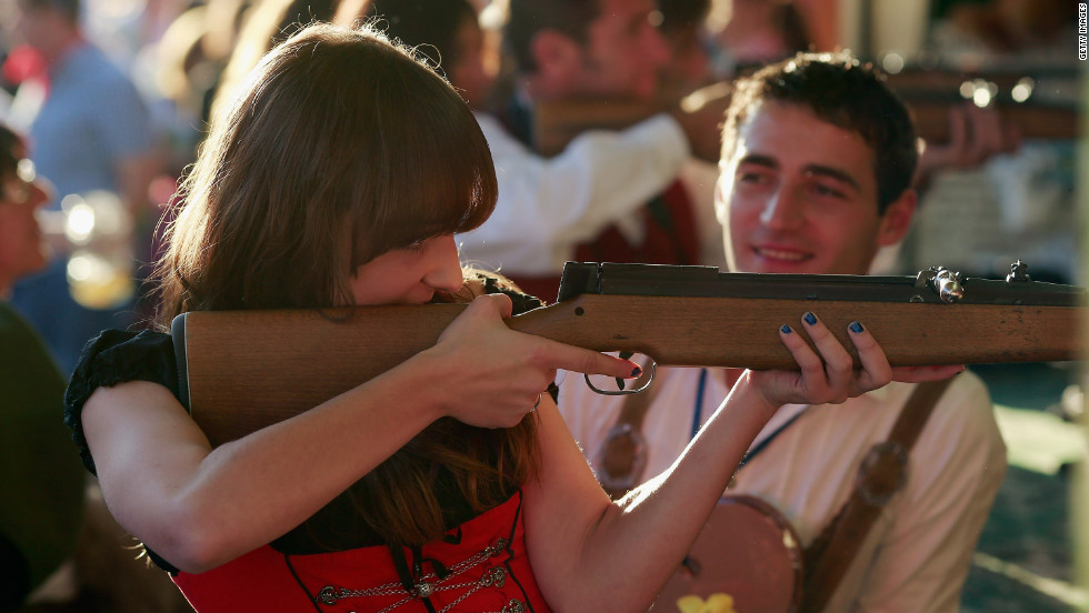 A girl wearing a Bavarian Dirndl dress fires a rifle at a shooting range at Oktoberfest.