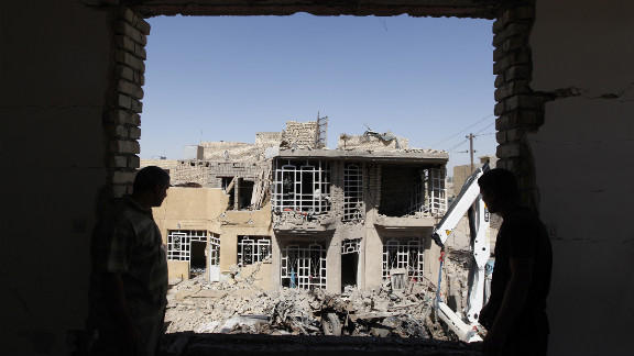 Residents look on as they stand at the site of a bomb blast in the town of Taji, north of Baghdad, Sunday.