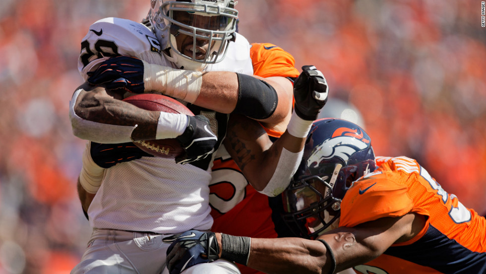 Darren McFadden of the Oakland Raiders is tackled for a loss by No. 95 Derek Wolfe and No. 52 Wesley Woodyard of the Denver Broncos on Sunday at Sports Authority Field Field at Mile High in Denver.