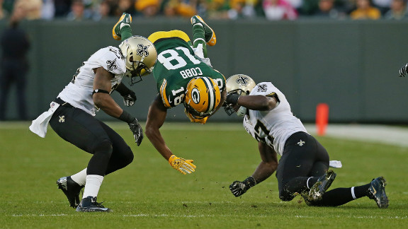 Randall Cobb of the Green Bay Packers flips in the air Sunday after being hit by Corey White, left, and Malcolm Jenkins of the New Orleans Saints.