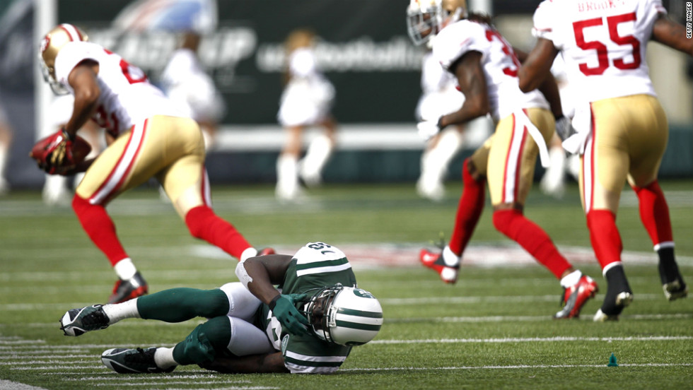 Santonio Holmes of the New York Jets writhes on the turf after fumbling a ball picked up by Carlos Rogers of the San Francisco 49ers on Sunday at MetLife Stadium in East Rutherford, New Jersey.
