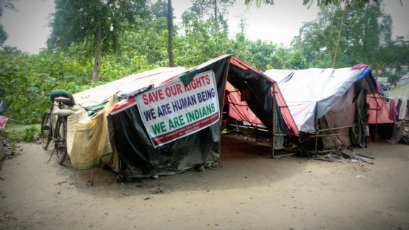 Relief camps set up in schools are overcrowded, and residents often need to set up makeshift tents on the surrounding grounds. In this Muslim camp, banners protest allegations that Muslim inhabitants in Assam are illegal immigrants from Bangladesh.