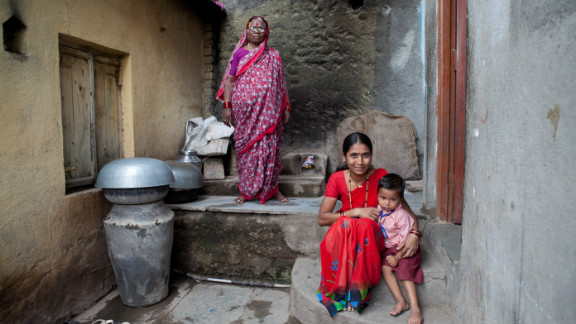 Sai, who is almost three years old, sits with mother and neighbor outside her home. Anganwadi workers counsel her mother about how, when and what to feed Sai to increase her weight.