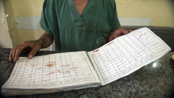 A doctor looks at the register of dead people, stained with blood, in a hospital in the eastern sector of the city of Aleppo on October 1, 2012.