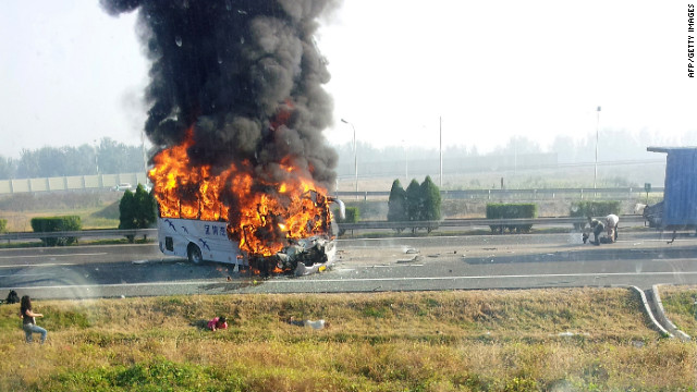 Flames leap from a tourist bus which crashed into a truck on an expressway in Tianjin, China, on Monday..
