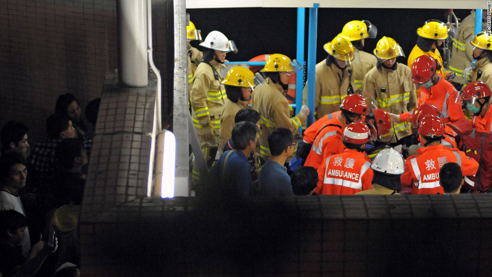 Local residents try to get a glimpse of rescue personnel as they tend to a victim Monday night. The incident happened around 8:20 p.m. local time, just off the coast of Lamma Island, southwest of Hong Kong.