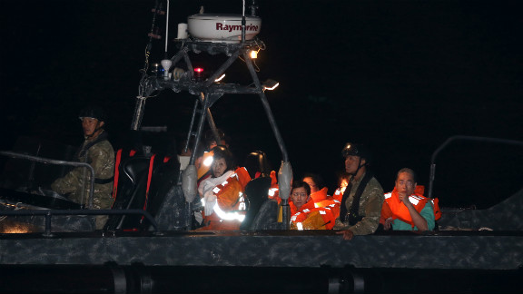 Survivors are transported to shore on a police boat late Monday.
