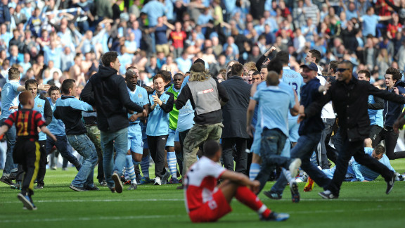 Players and fans of Manchester City celebrate after winning their first English title since 1968. City trailed Queens Park Rangers 2-1 but scored two stoppage time goals to win 3-2 - and so deny city rivals Manchester United the title. The success echoed United