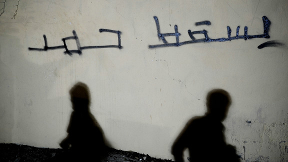 """Shadows of Bahraini Shiites are seen on a wall with the Arabic writing """"Down with Hamad"""" west of Manama on September 26."""