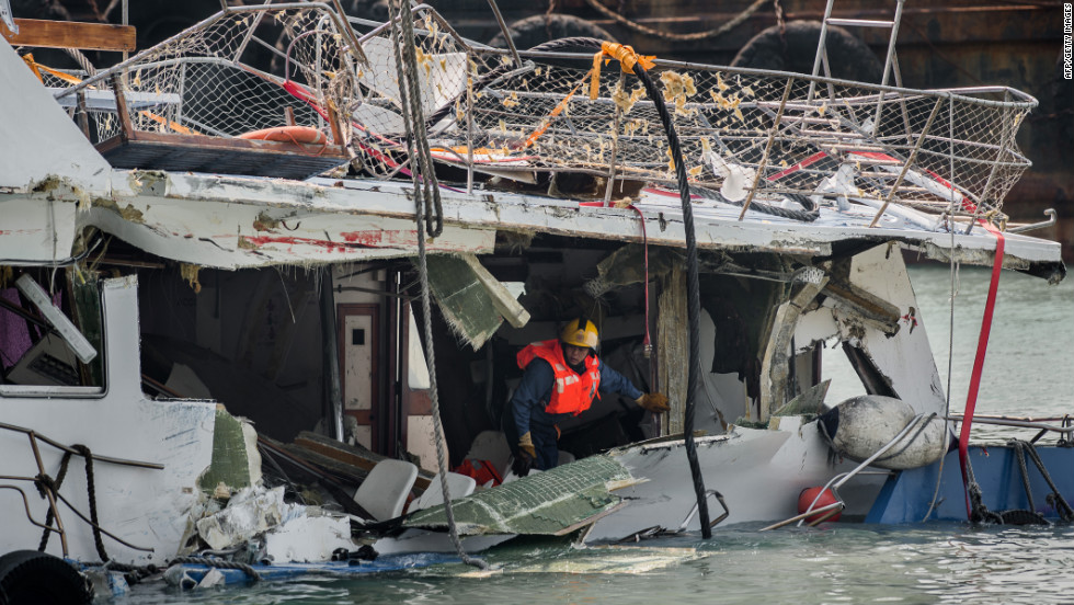 A fireman inspects the back end of the badly damaged Lamma IV passenger boat two days after the collision.