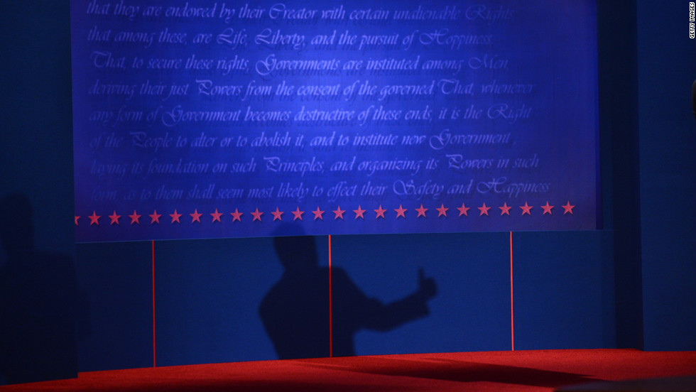 Romney's shadow is projected beneath text from the Declaration of Independence at the University of Denver's Magness Arena.
