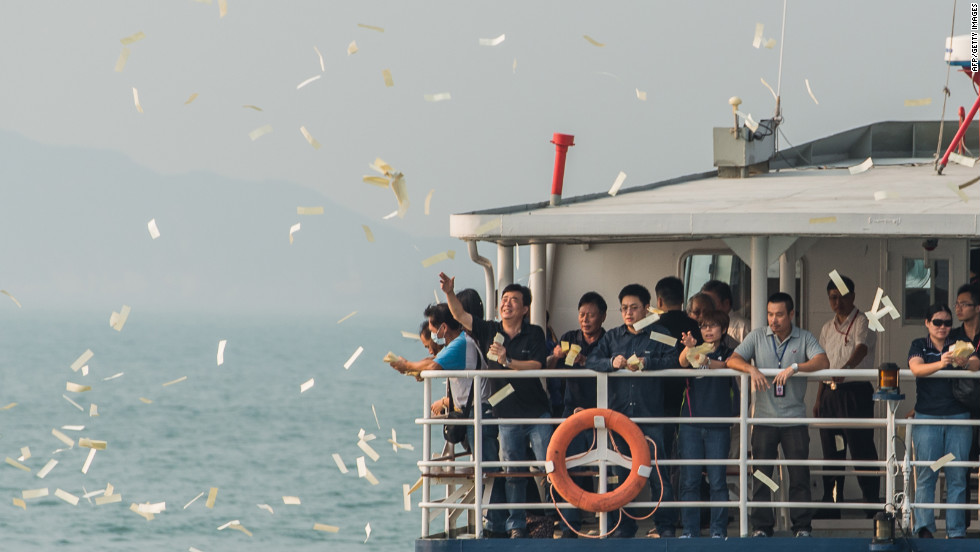 Mourners throw paper offerings into the sea Thursday during a ceremony held for the victims of the ferry collision.