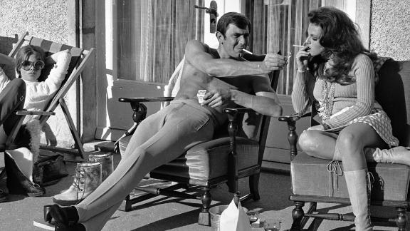 George Lazenby offers co-star Helena Ronee a light during the filming of ""