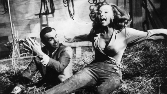 """Sean Connery's Bond is  up to his tricks with actress Honor Blackman as Pussy Galore during the filming of  """"Goldfinger"""" in 1964."""