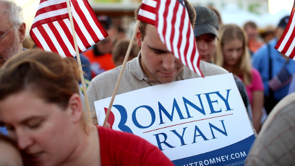 Romney supporters bow their heads in prayer during Thursday