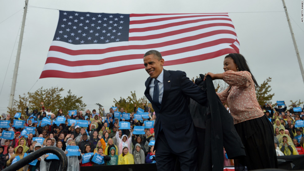 Obama is assisted with putting on a raincoat onstage during a campaign rally at Cleveland State University on Friday.