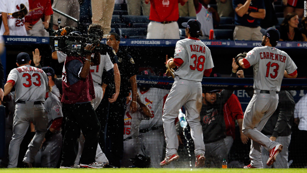 Cardinals Pete Kozma, left, and Matt Carpenter run into the dugout as debris rains onto the field.