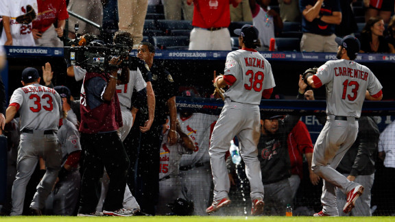 Cardinals Pete Kozma, left, and Matt Carpenter run into the dugout as debris rains onto the field.