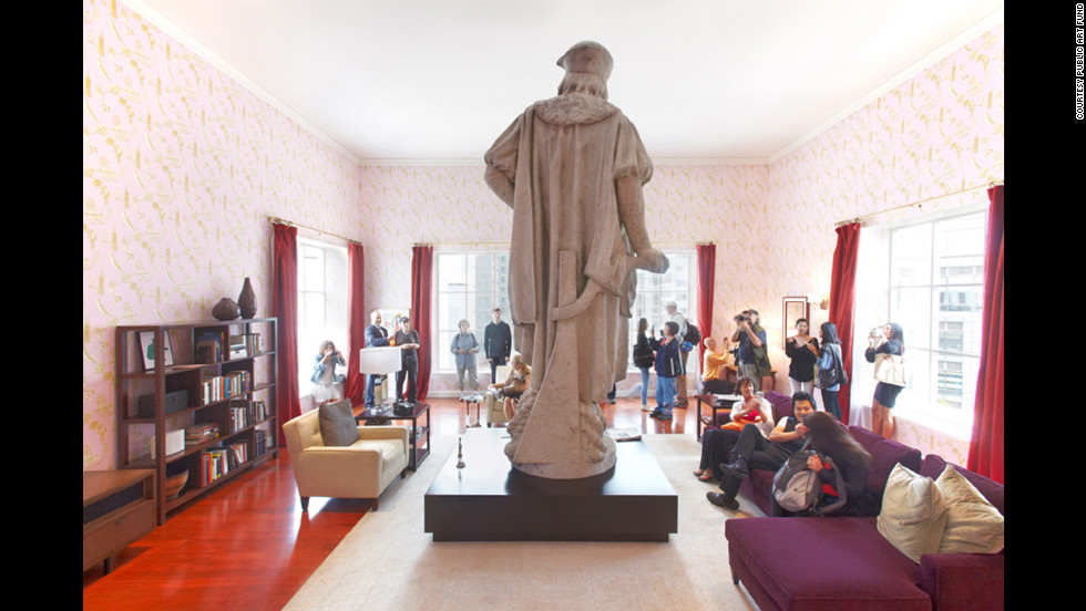 "The art installation ""Discovering Columbus"" takes the form of a modern New York living room surrounding the 13-foot marble statue of Christopher Columbus."