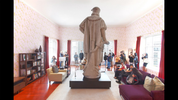 """The art installation """"Discovering Columbus"""" takes the form of a modern New York living room surrounding the 13-foot marble statue of Christopher Columbus."""
