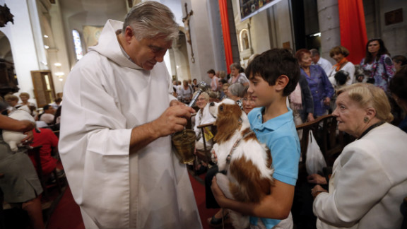 Priest Gil Florini blesses a dog during Sunday