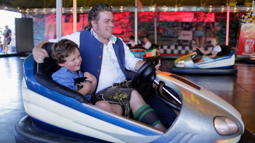 A father and son dressed in traditional Bavarian clothing ride in a bumper car on Friday.