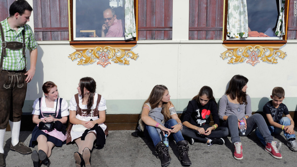Young people, some dressed in traditional Bavarian clothing, wait outside a duck roast beer tent at the Oktoberfest beer festival in Munich, Germany, on Saturday, October 6.