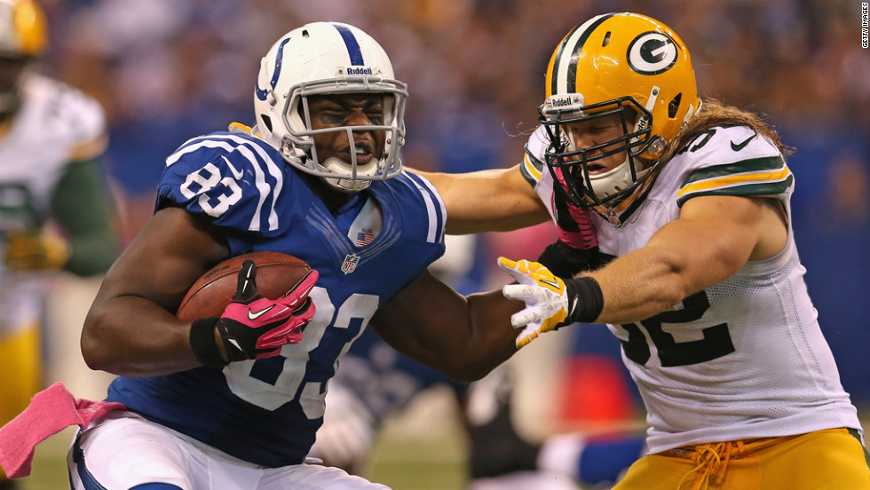 Clay Matthews of the Green Bay Packers tackles Dwayne Allen of the Indianapolis Colts on Sunday at Lucas Oil Stadium in Indianapolis.