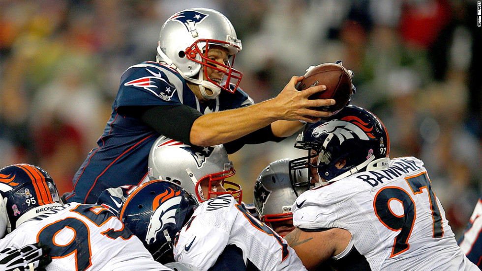 Quarterback Tom Brady of the New England Patriots leaps for a touchdown against the Denver Broncos on Sunday at Gillette Stadium in Foxboro, Massachusetts.