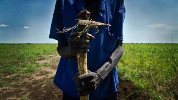 A farmer holds a plow  near the Sudan-South Sudan border.