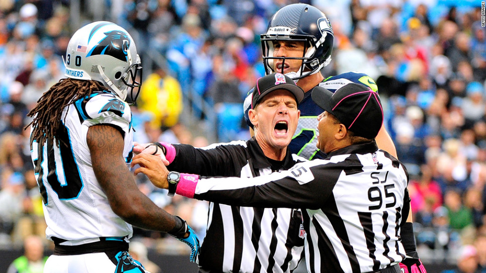 Officials break up a skirmish Sunday between Charles Godfrey of the Carolina Panthers and Gary Barnidge of the Seattle Seahawks.