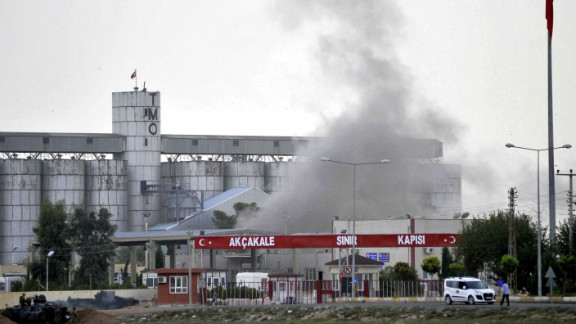 Smoke rises at a border gate in  Akcakale, Turkey, near the Syrian border on Sunday, October 7, after a shell fired from Syria. Turkey fired on Syrian government targets in response. No was injured in Sunday