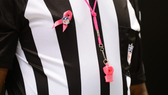 An official wears a pink ribbon and whistle for Sunday