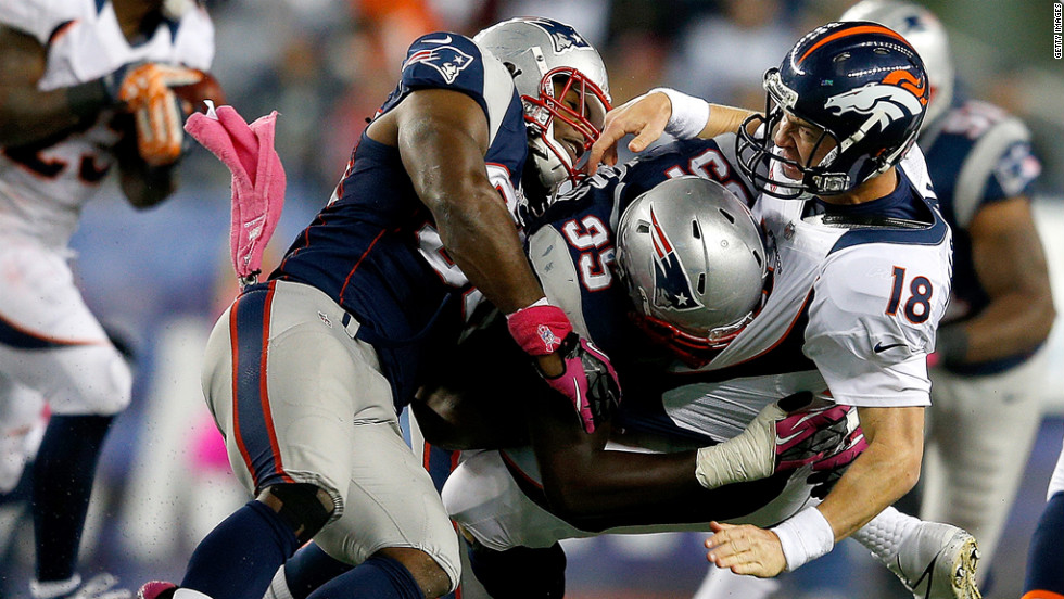 Jermaine Cunningham, left, and Chandler Jones of the New England Patriots rough up Peyton Manning of the Denver Broncos after he released a pass during the second half on Sunday.