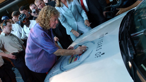 Lead singer Plant autographs the hood of a Cadillac CTS in Detroit in 2002. Led Zeppelin's music has been featured in Cadillac commercials.