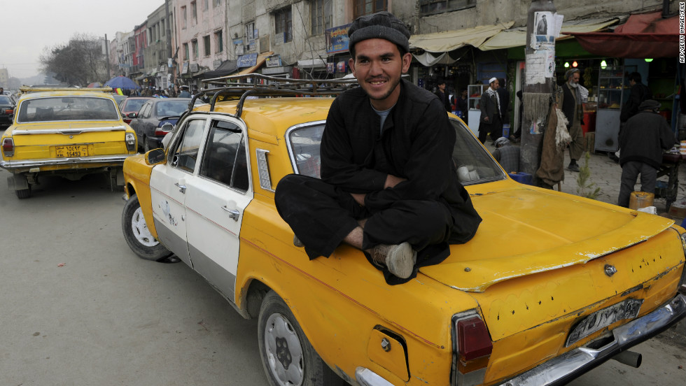 An Afghan taxi driver sits on the back of a Russian-made cab in Kabul in 2011. Many Afghans fear the war here is dropping down America's list of priorities.