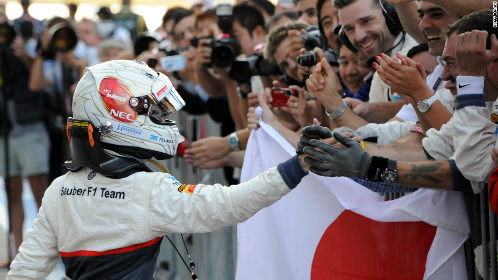 Kobayashi celebrates his historic podium placing with members of the Sauber team.