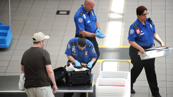 A Transportation Security Administration(TSA) agent checks the luggage of a passenger(L) May 2, 2011 at Orlando International Airport in Orlando, Florida. Security in airports and train stations has been increased in the wake of the death of Osama bin Laden. AFP PHOTO/Stan HONDA (Photo credit should read STAN HONDA/AFP/Getty Images)